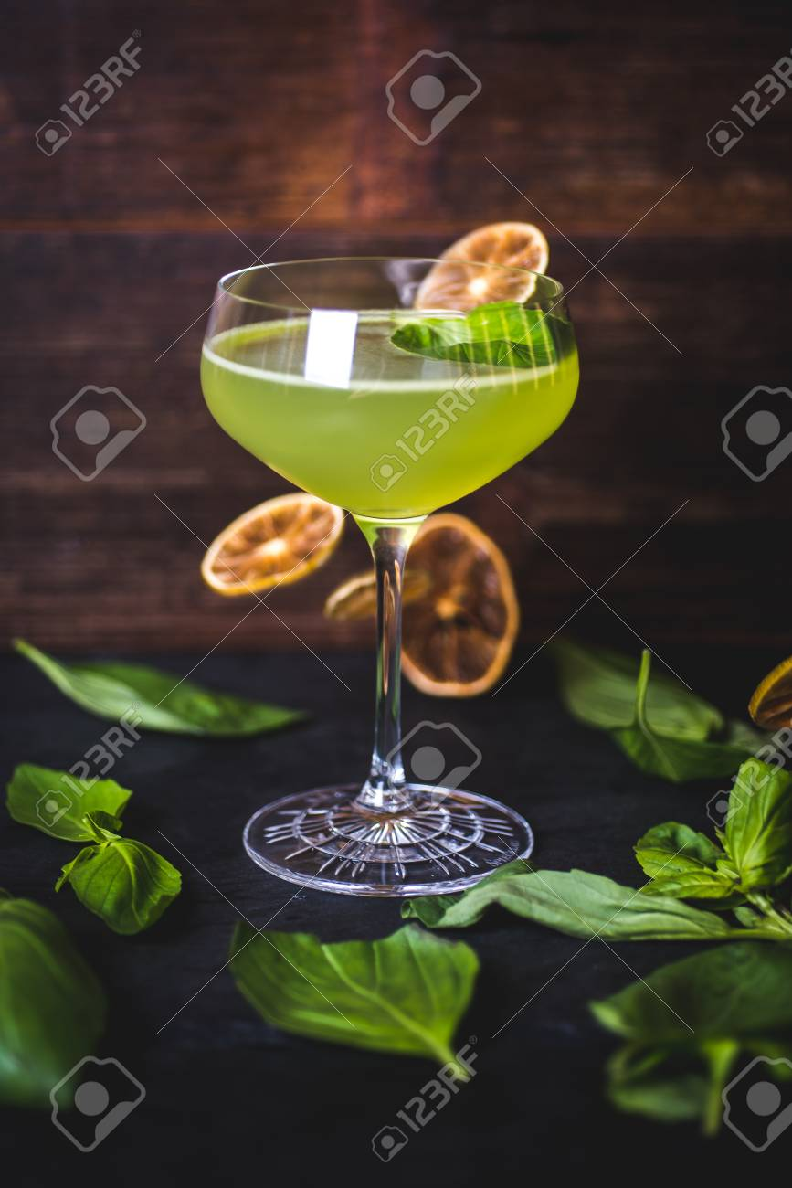 Cocktail on the background of falling lemon slices. - 99535129