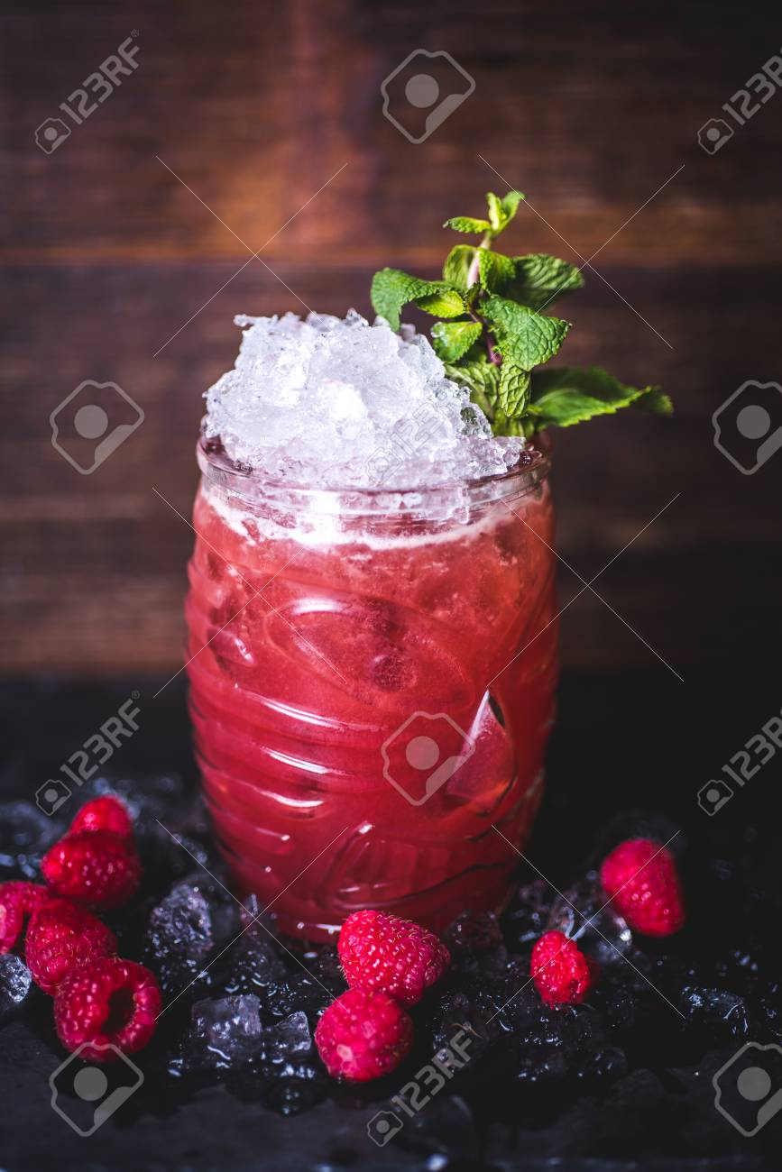 Raspberry cocktail with ice and mint is on the table. - 99535132