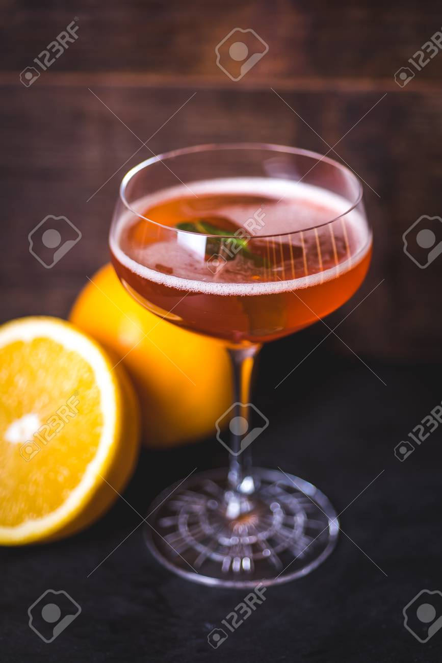 A glass with a drink and a sheet of mint. - 99535133