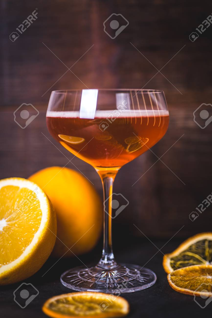 Oranges are reflected on the glass of a glass with a drink. - 99535730
