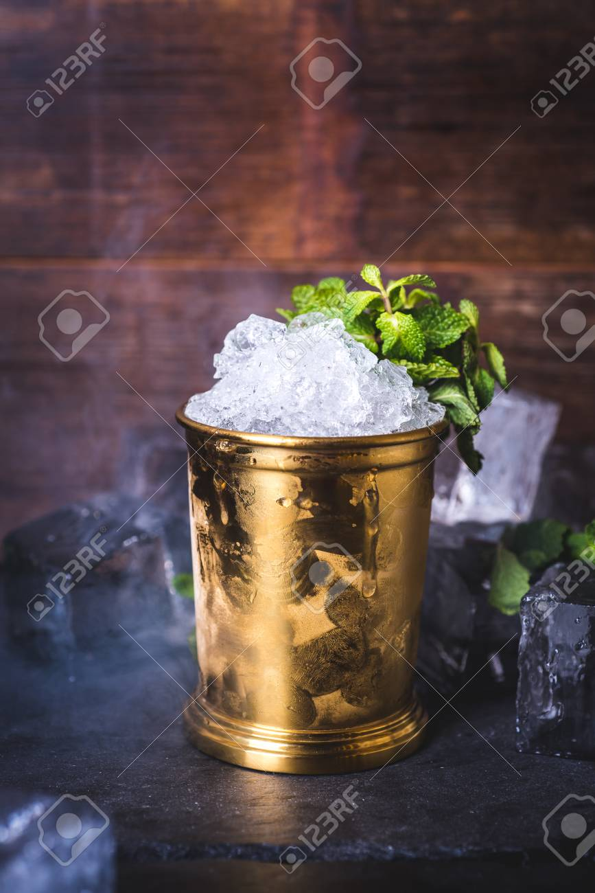 A tin can with ice is decorated with a sprig of mint. - 99535740