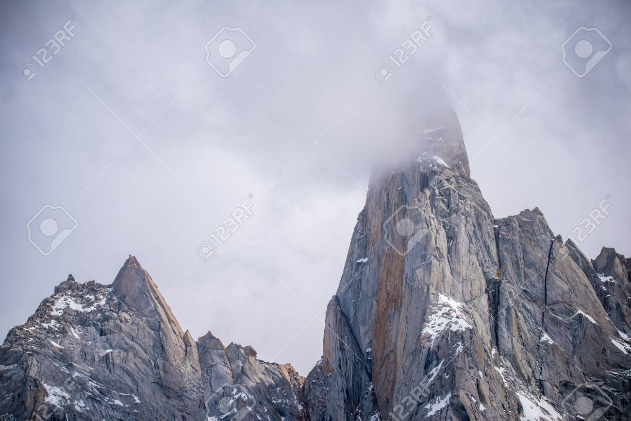 The cloud envelops the top of the rocks. The snow lies on the ledges of the rocks. Sunlight reflects on the rocks. - 107212963