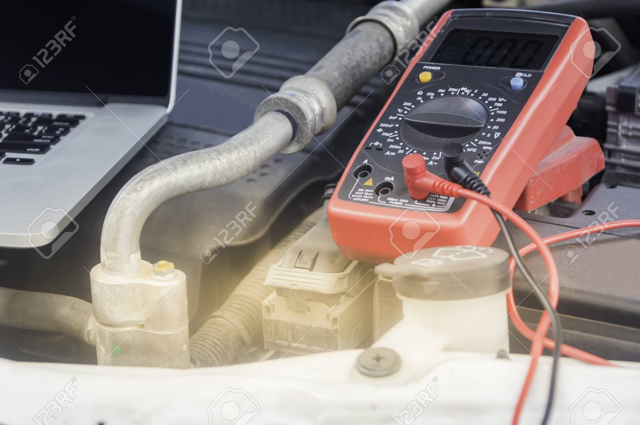 Auto Mechanic Uses A Multimeter Voltmeter To Check The Voltage