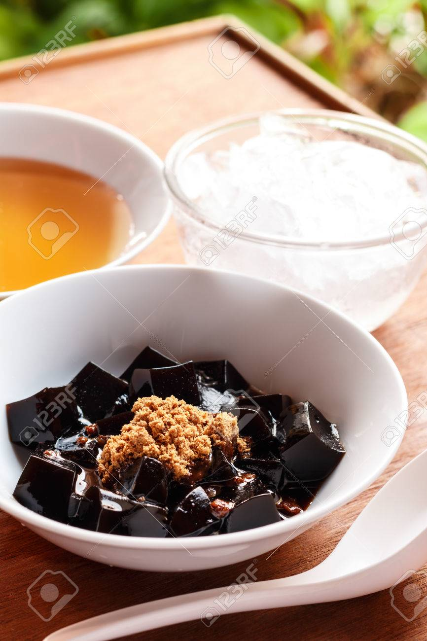 grass jelly dessert herbal gelatin , syrup, ice, and brown sugar on the wooden background. Chinese style. - 46534647