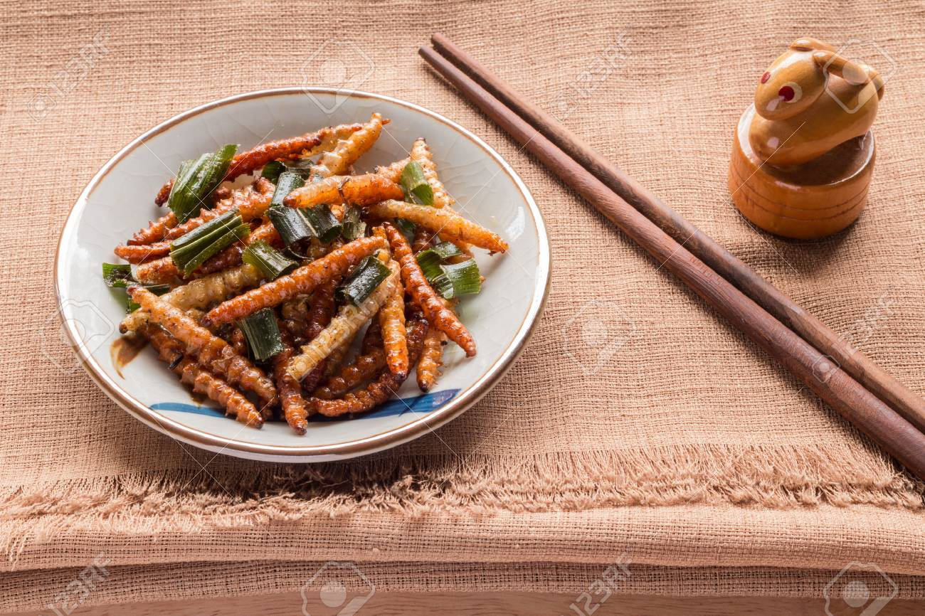 Fried insects - Wood worm insect crispy with pandan after fried and add a light coating of sauce and garnish Thai pepper powder and chopsticks on brown cloth background, select focus - 61935575
