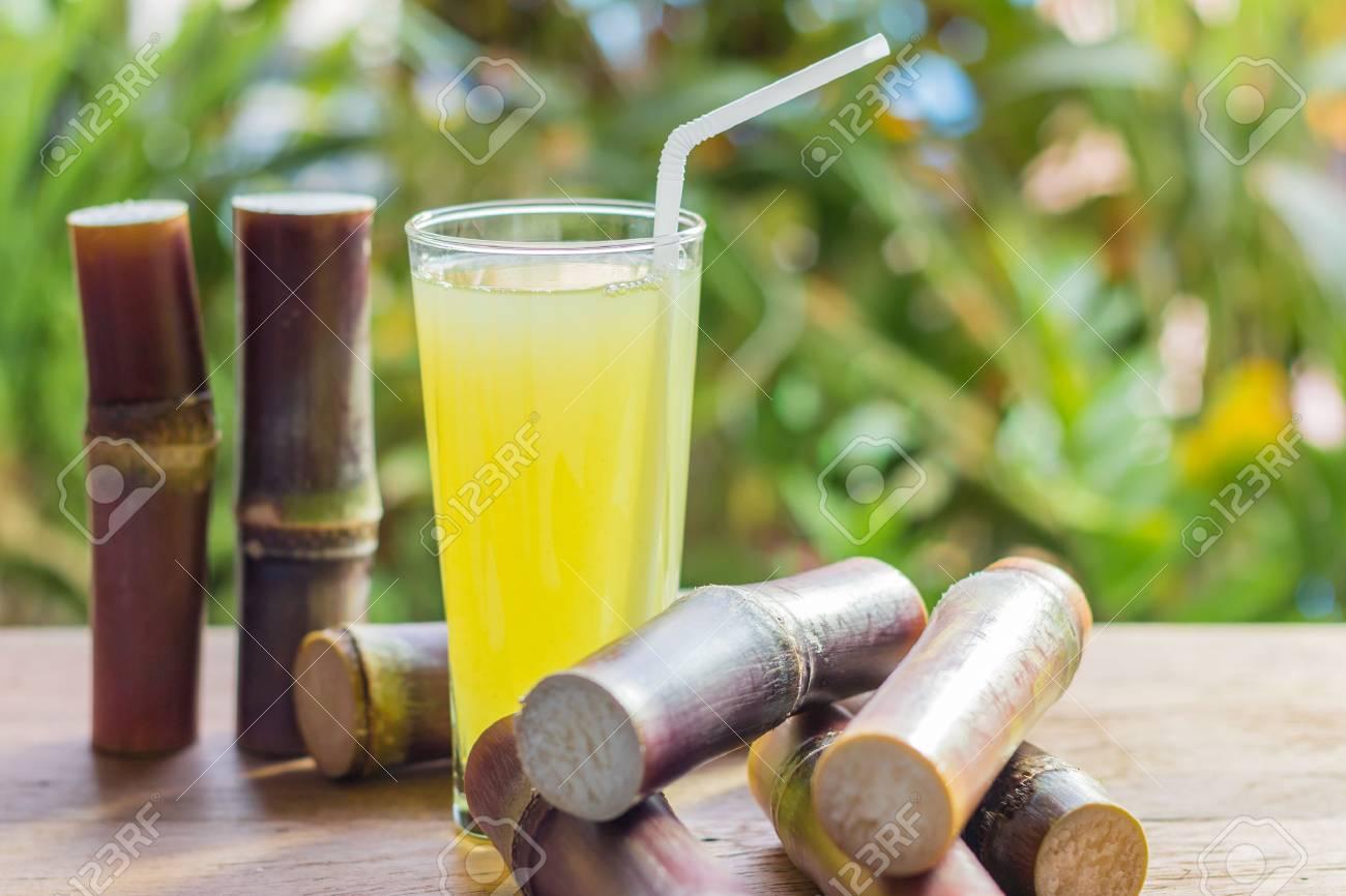 Sugarcane fresh juice with piece of sugarcane on wooden background. Closeup image / Selective focus - 67378226