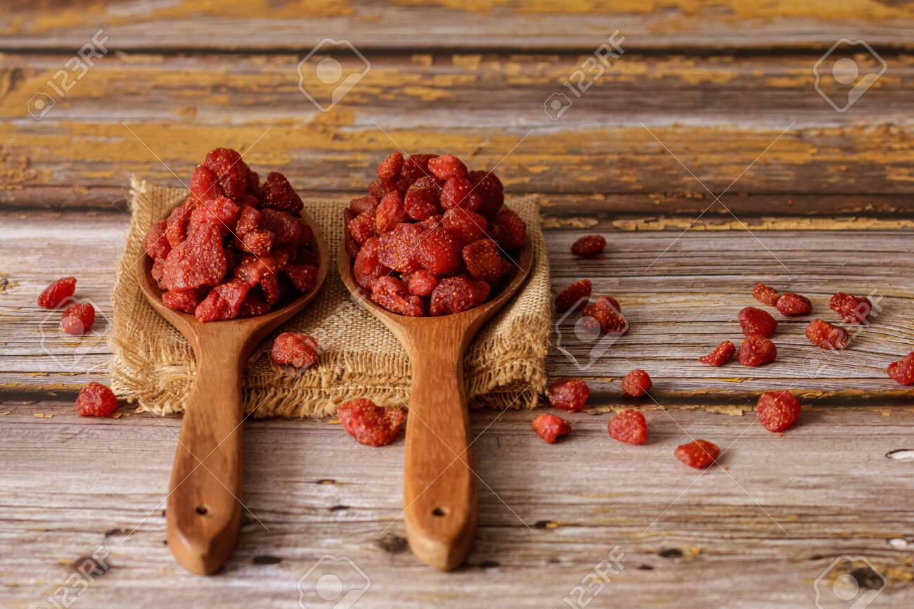 Dried strawberries in a wooden ladles with an old wooden background. - 149188989