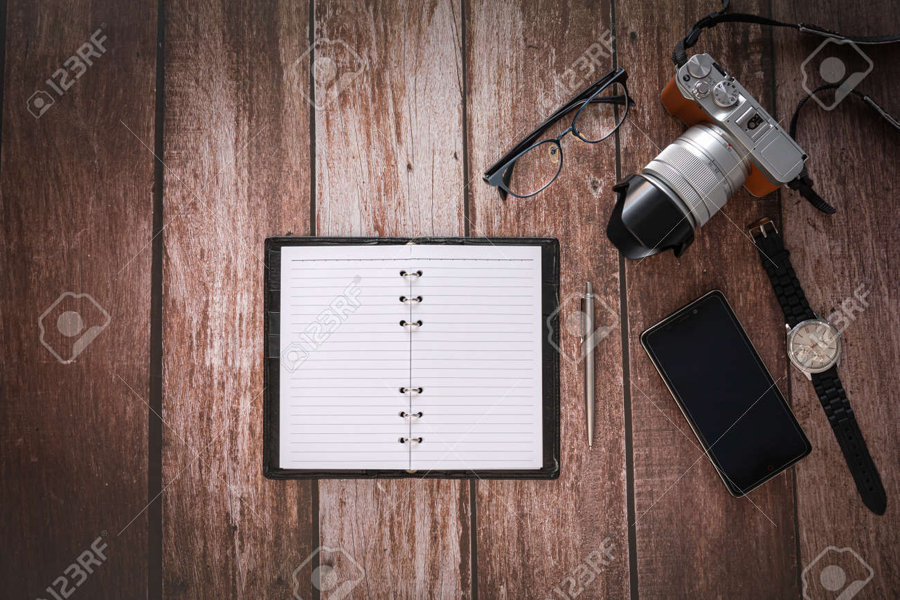 Overhead view of Traveler's accessories on wooden table background with Photo camera, Smart phone, Glasses and Note book with copy space. traveling concept background. Flat lay. - 163125178