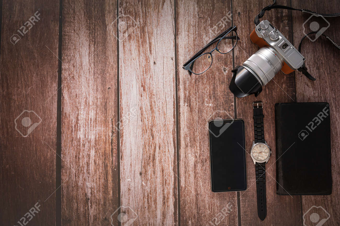 Overhead view of Traveler's accessories on wooden table background with Photo camera, Smart phone, Glasses with copy space. traveling concept background. Flat lay. - 163135782