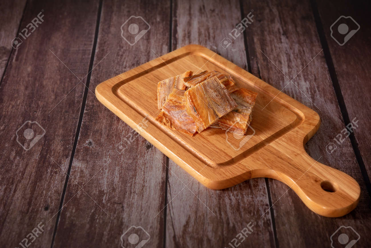 Dried fish fillet on a cutting board with a wooden dark background. Thai food concept. - 166001307