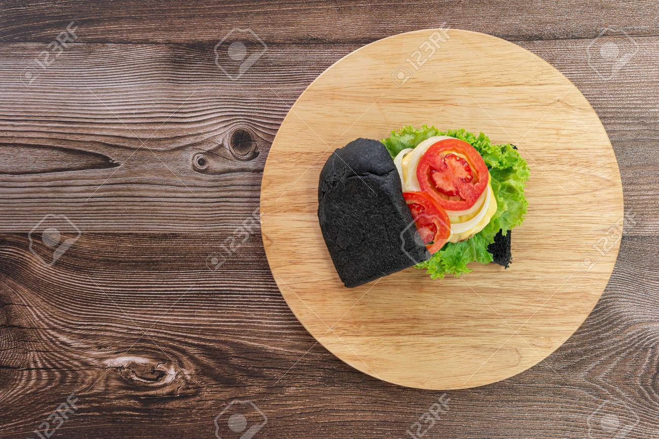 Black bread sandwich on a wooden kitchen board background. Top view. - 166001343