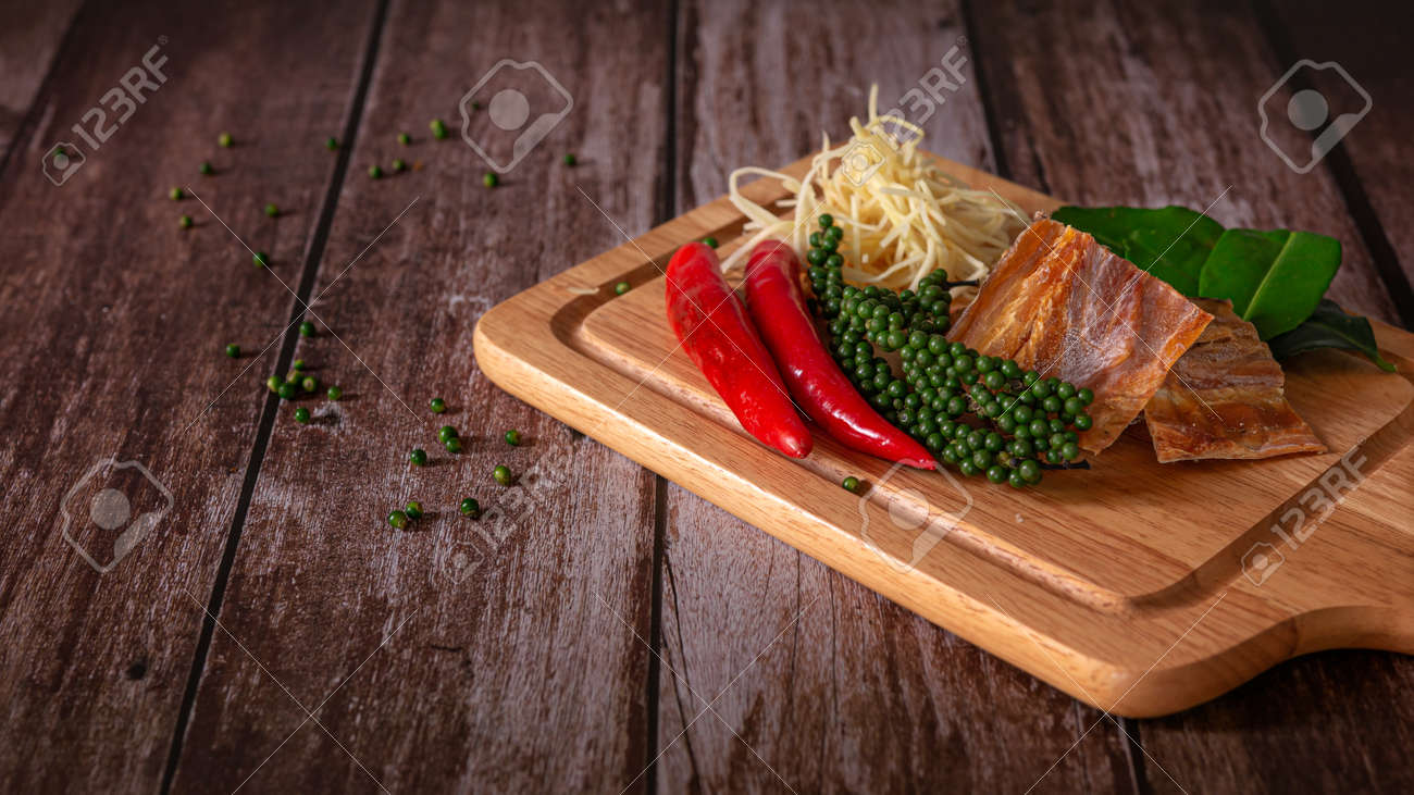 Spices with ingredients, Stir-Fried Spicy and herb with dried fish fillet on a cutting board with wooden dark background. Thai food concept. - 166001378