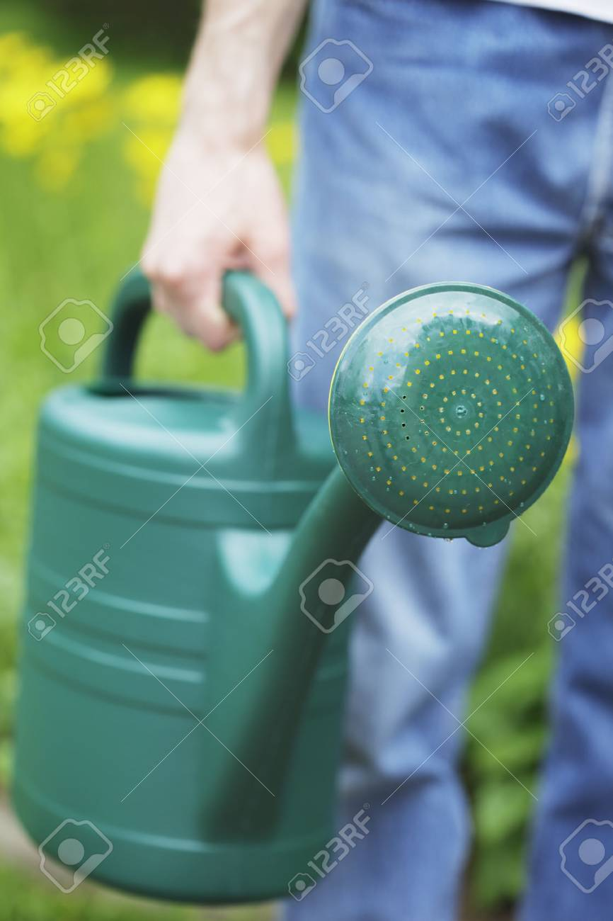 A Man holding a green plastic watering can in his hand. Short depth of field, sharpness is in the spout. Stock Photo - 5091276