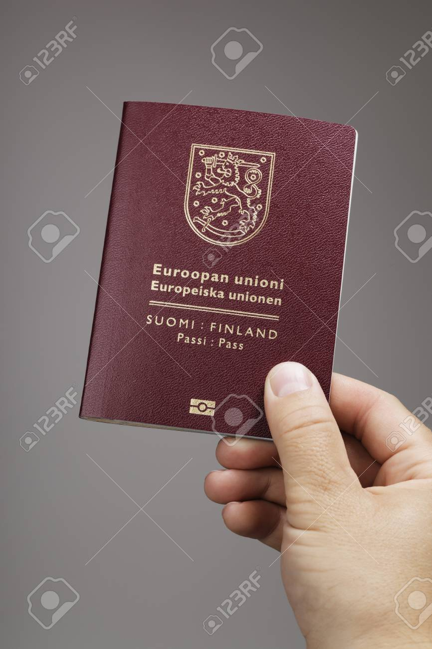 Man holding a Finnish (Finland) passport ih his hand. This is the new (2013) of the passport. Stock Photo - 22436877