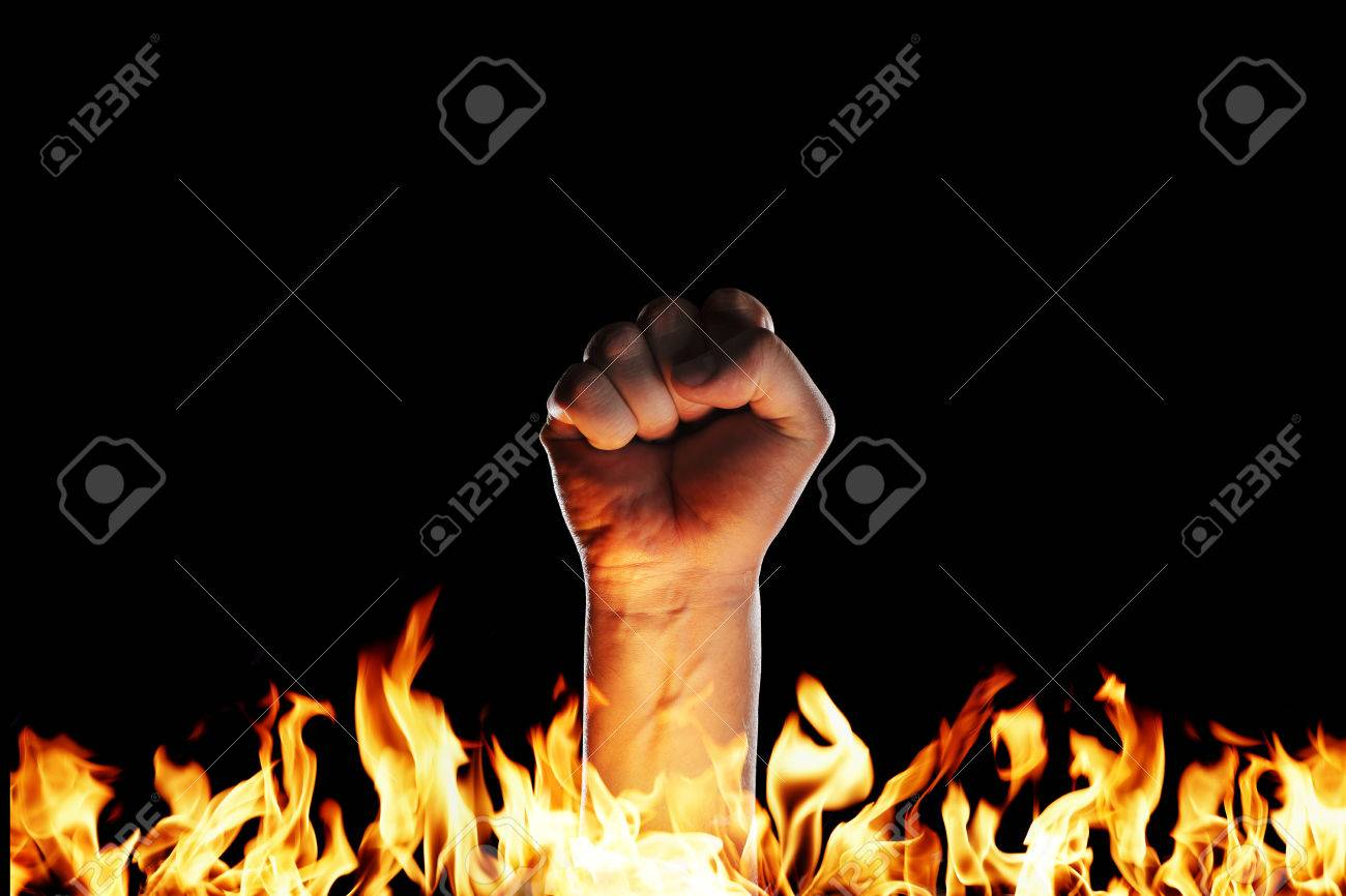 Hand in a fist emerging from a sea of fire Stock Photo - 23303932