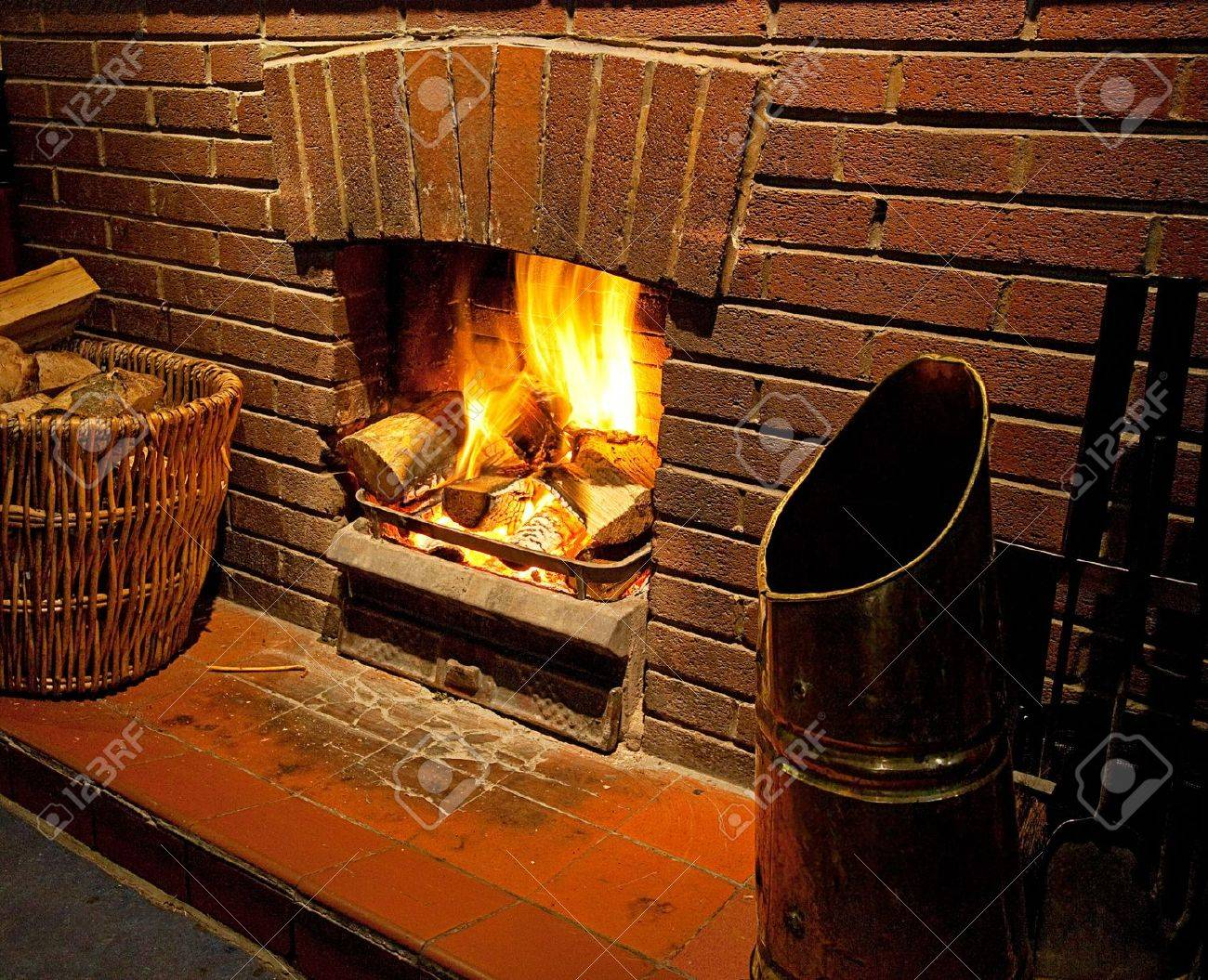 cosy bright roaring log fire with brick surround glowing with