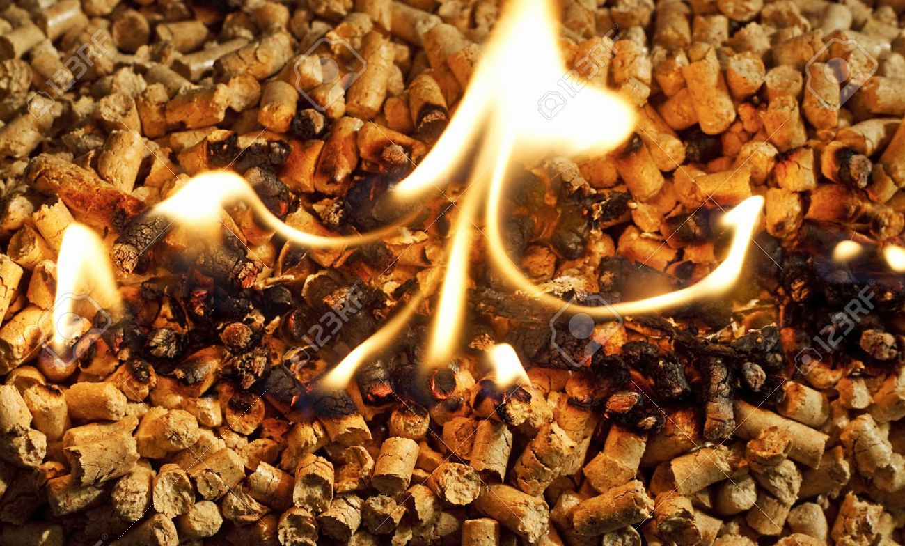 burning wood chip pellets a renewable source of energy becoming popular as a green environmentally friendly fuel for stoves which provide household heating - 18243850