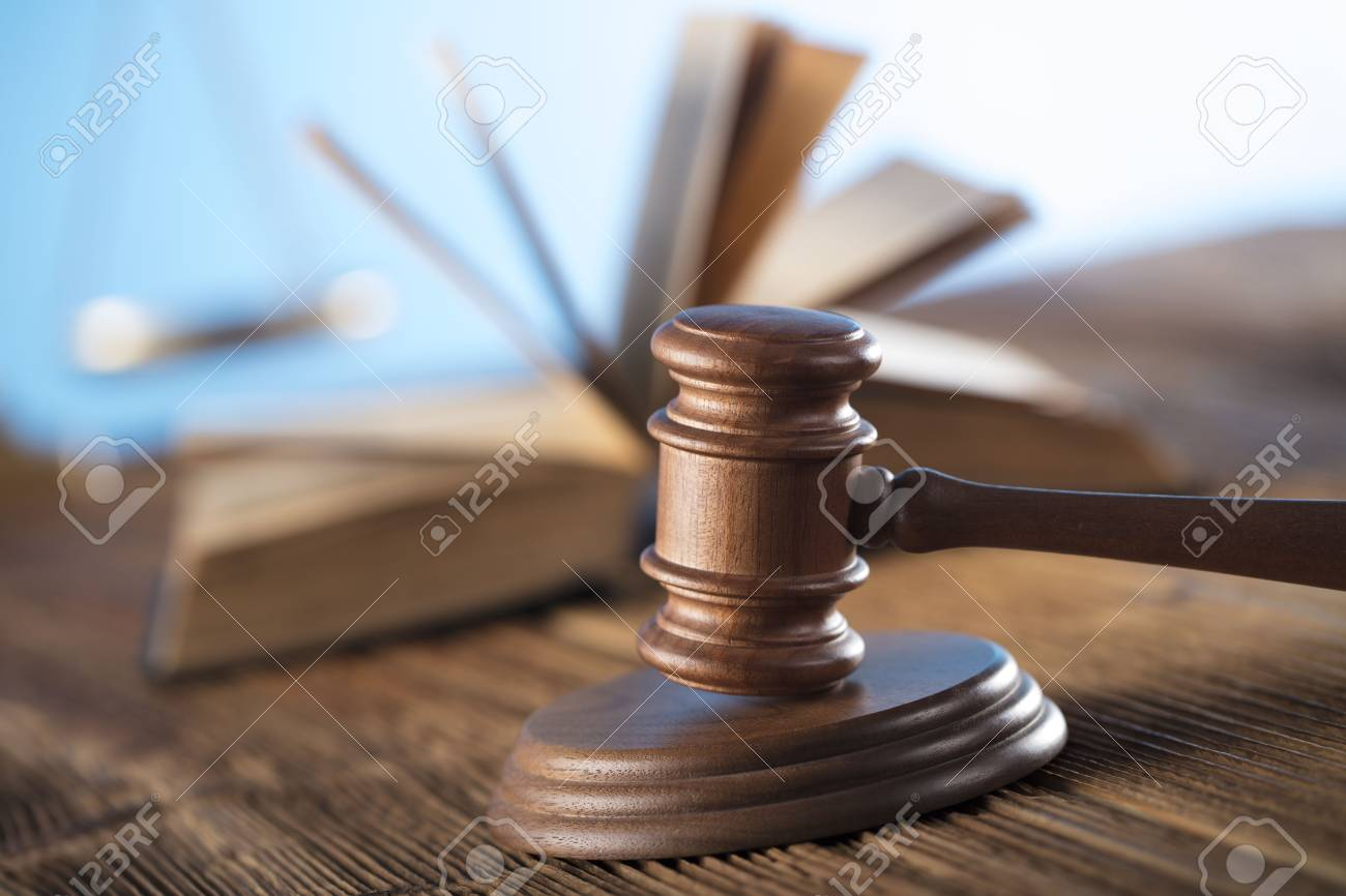 Judge concept. Mallet of the judge, justice scale and books on wooden desk and blue background. - 89483102