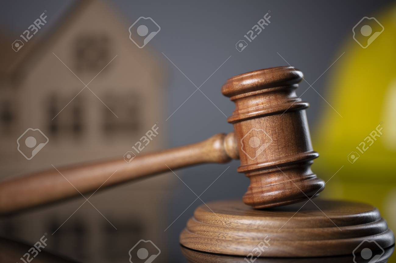 Construction law concept. Wooden gavel on the gray background with the house model and the yellow hardhat. - 119667709