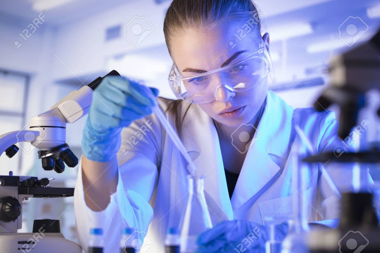 Science research concept. Young scientist during experiment and using microscope in modern laboratory. Glass tubes and beakers. - 144265072