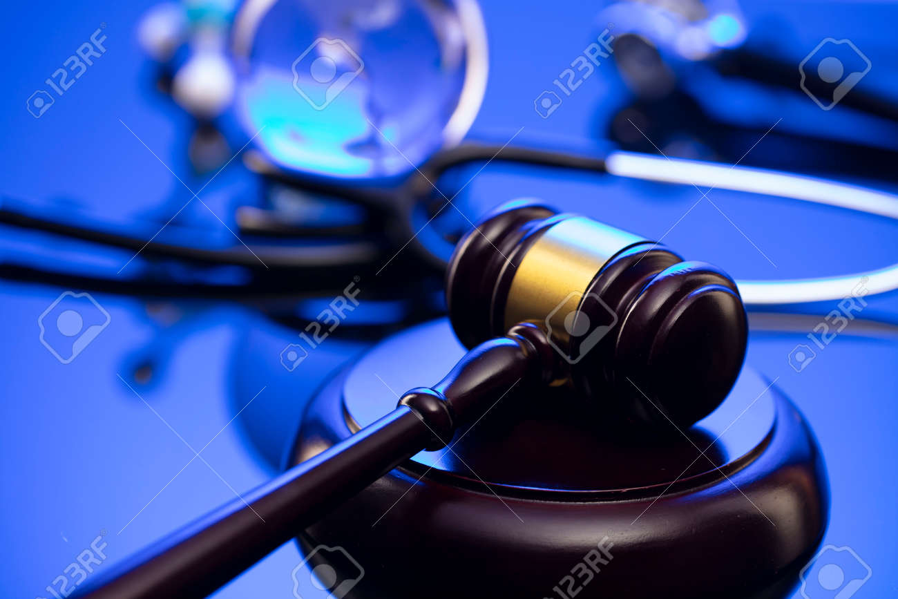 Medical law concept. Gavel and stethoscope on the glass table. Blue light. - 167642215