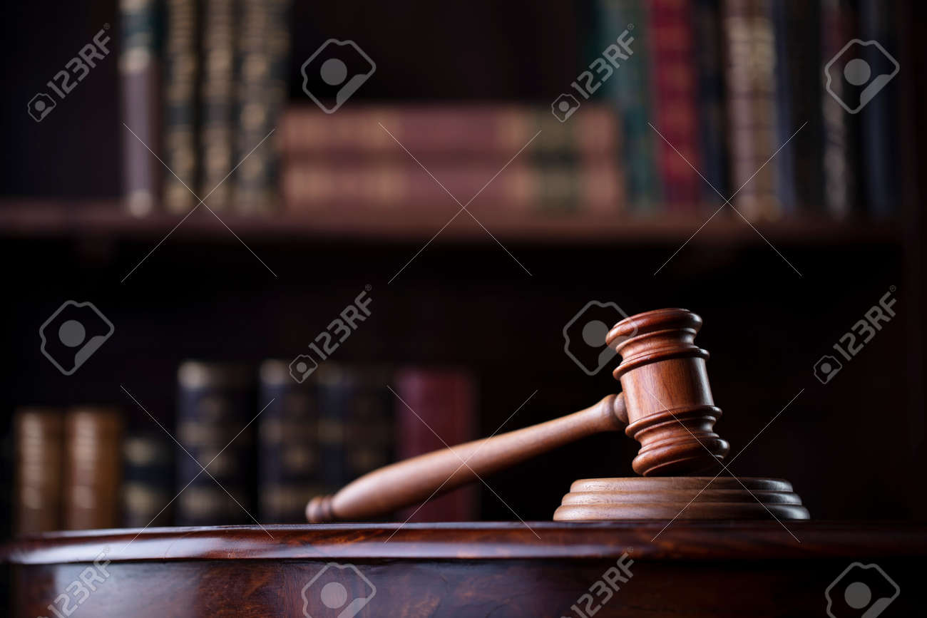 Lawyer office. Gavel on brown shining desk and collection of legal books in the bookshelf. - 168775421
