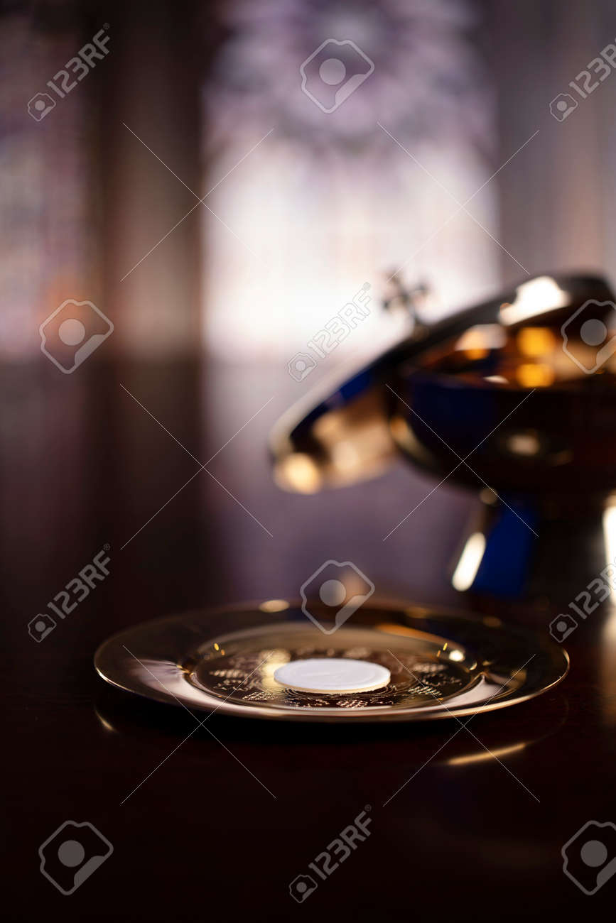 First Holy Communion. Catholic religion theme. Crucifix, the Croass and Golden chalice and wafer on the altar. - 168772310
