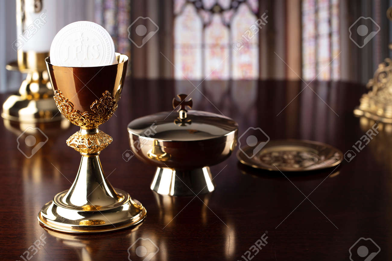 First Holy Communion. Catholic religion theme. Crucifix, the Croass and Golden chalice and wafer on the altar. - 168772311