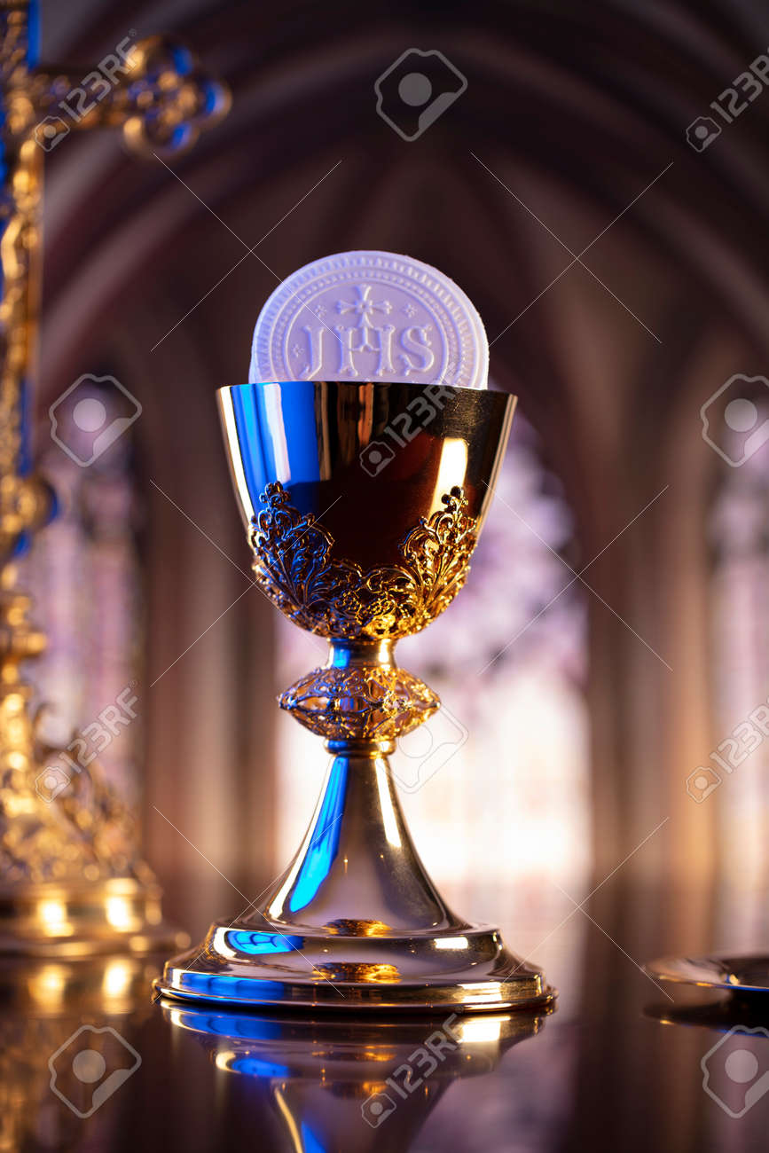 First Holy Communion. Catholic religion theme. Crucifix, the Croass and Golden chalice and wafer on the altar. - 168772313