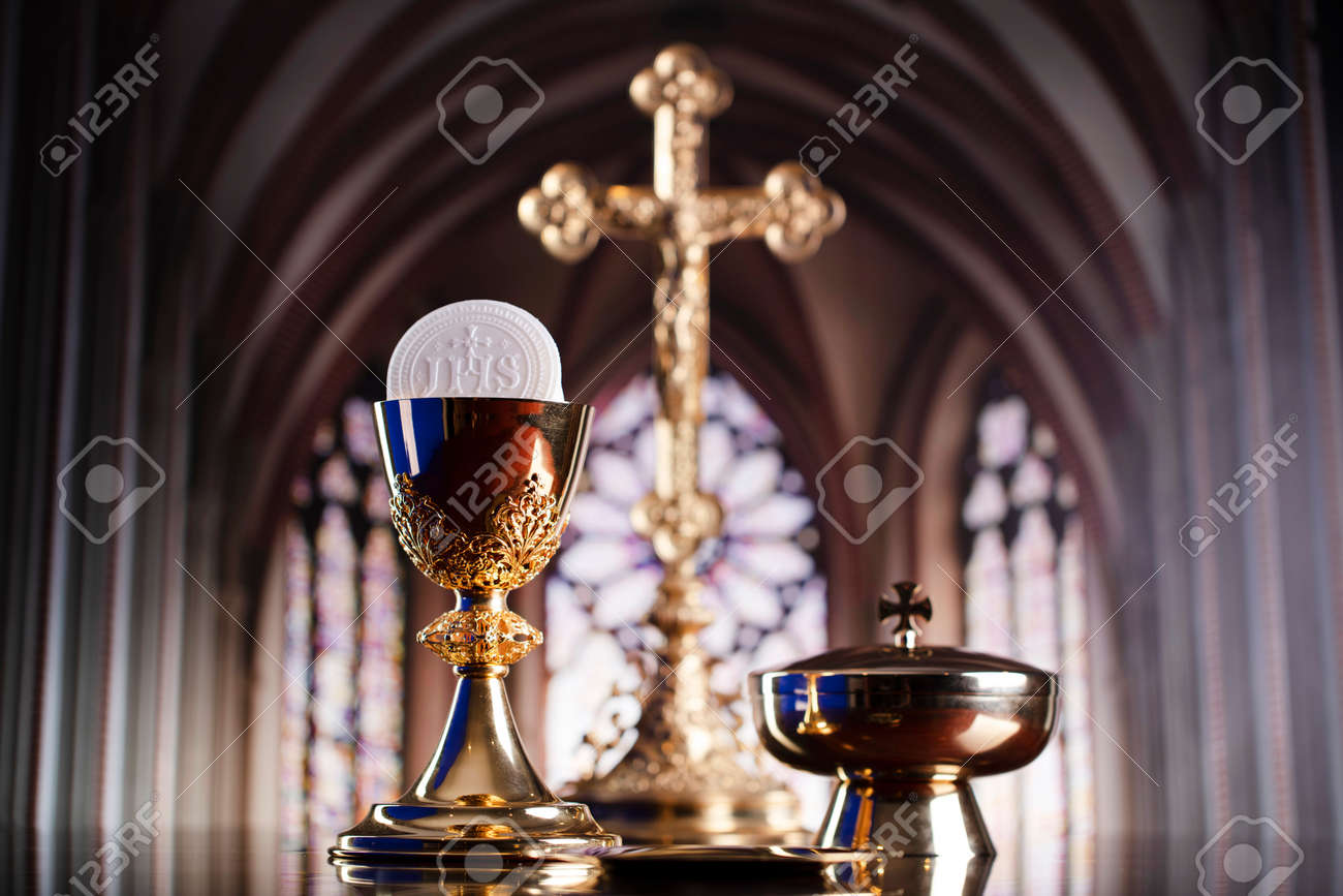 First Holy Communion. Catholic religion theme. Crucifix, the Croass and Golden chalice and wafer on the altar. - 168775340