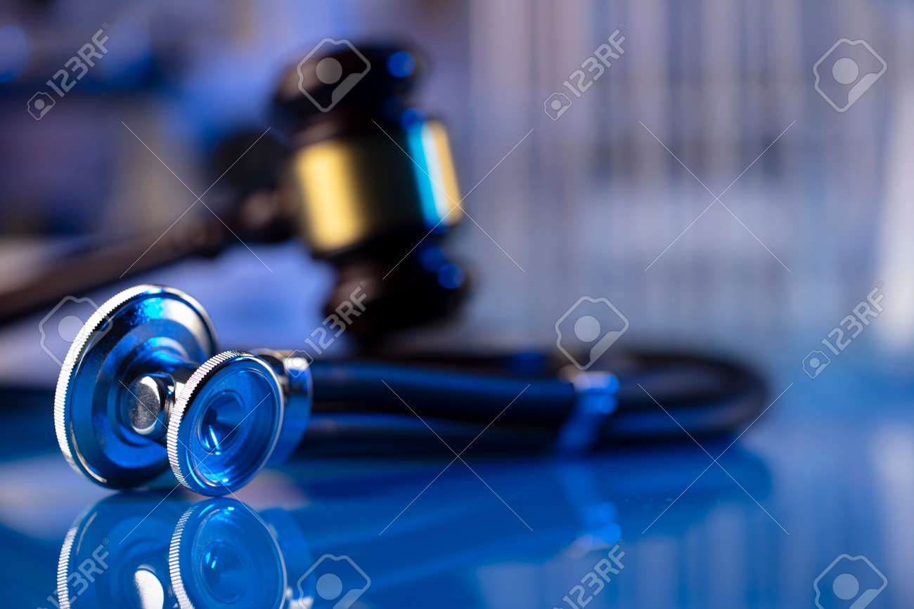 Medical law concept. Gavel and stethoscope on the glass table. Blue light. - 169346695