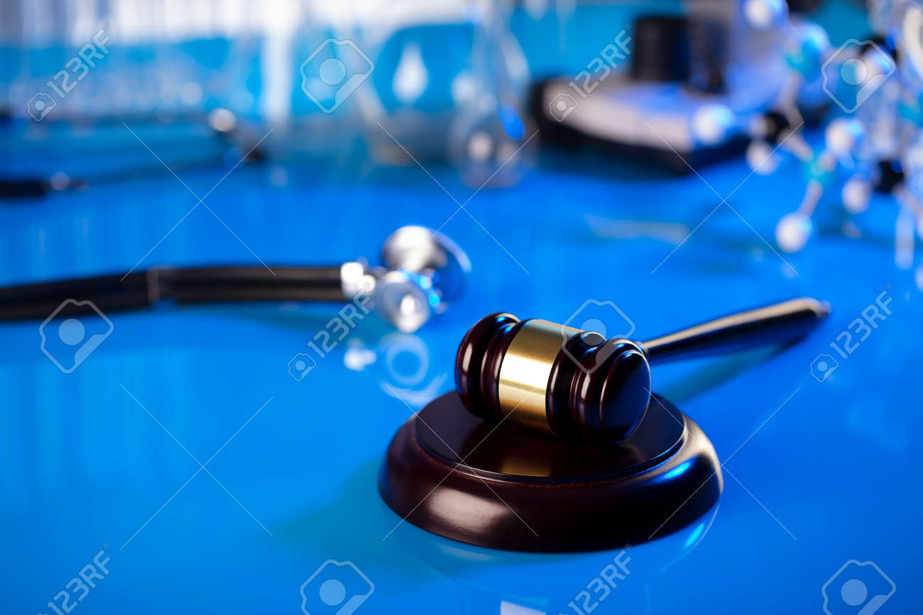 Medical law concept. Gavel and stethoscope on the glass table. Blue light. - 169346719