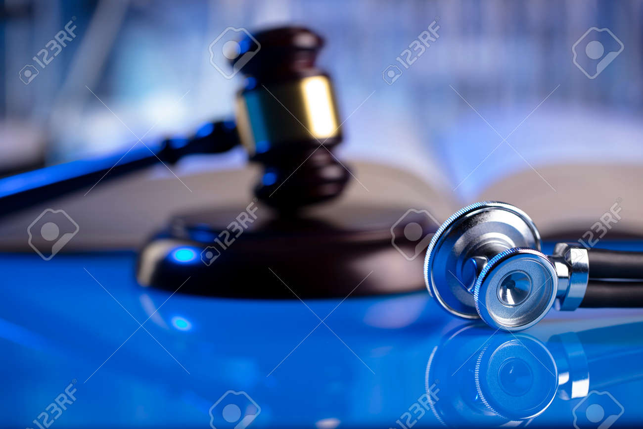 Medical law concept. Gavel and stethoscope on the glass table. Blue light. - 169346720