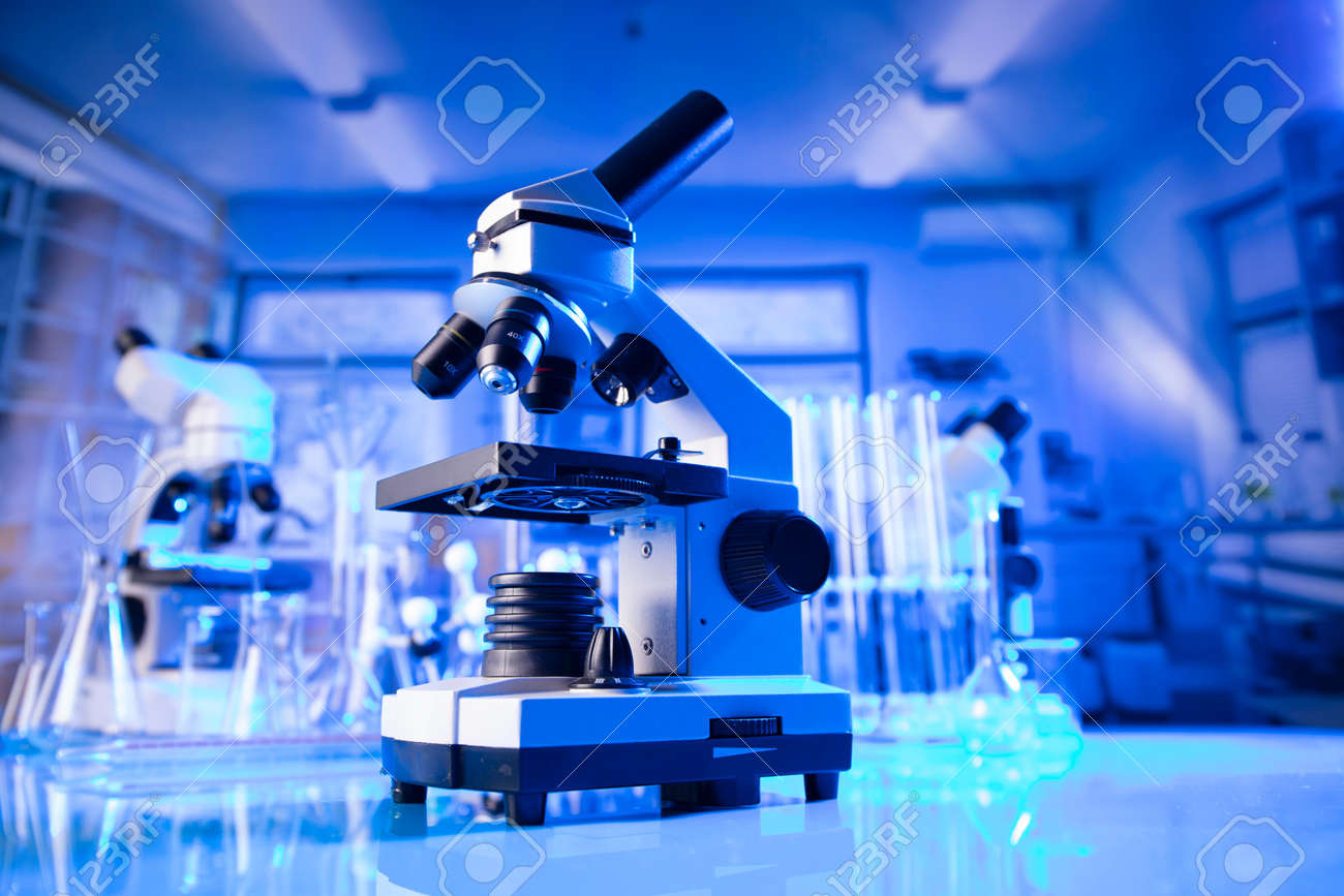 pandemic theme. Science research concerning fast tests and anti-vaccine. Microscope, beakers and test tubes in the scientific laboratory. - 169346784