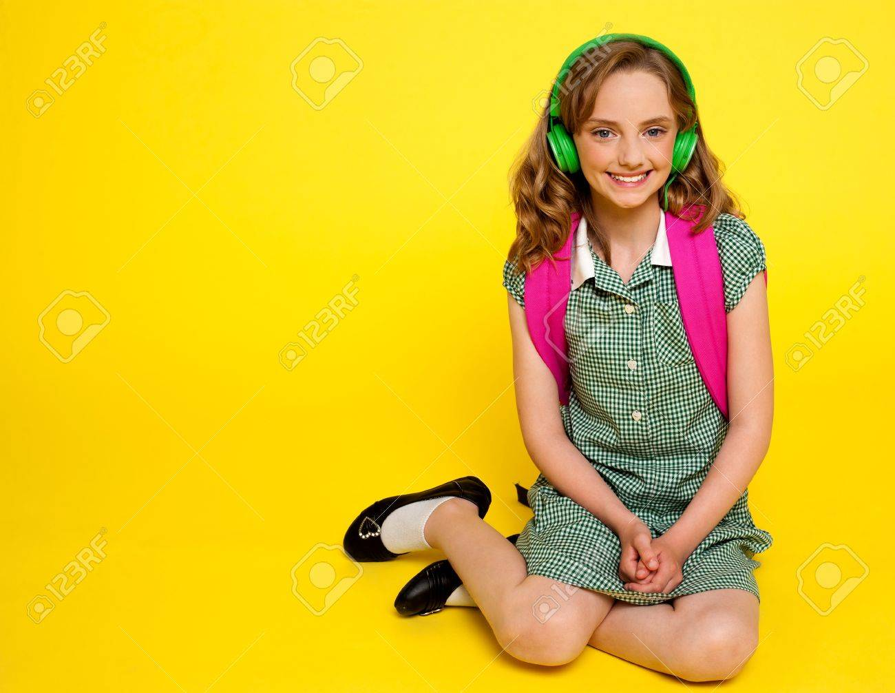 Pretty girl kid listening to music. Seated on floor. All on yellow background Stock Photo - 14337026
