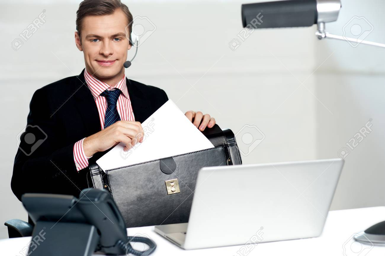 Male call centre executive arranging paper works and keeping them safely in bag Stock Photo - 14382599