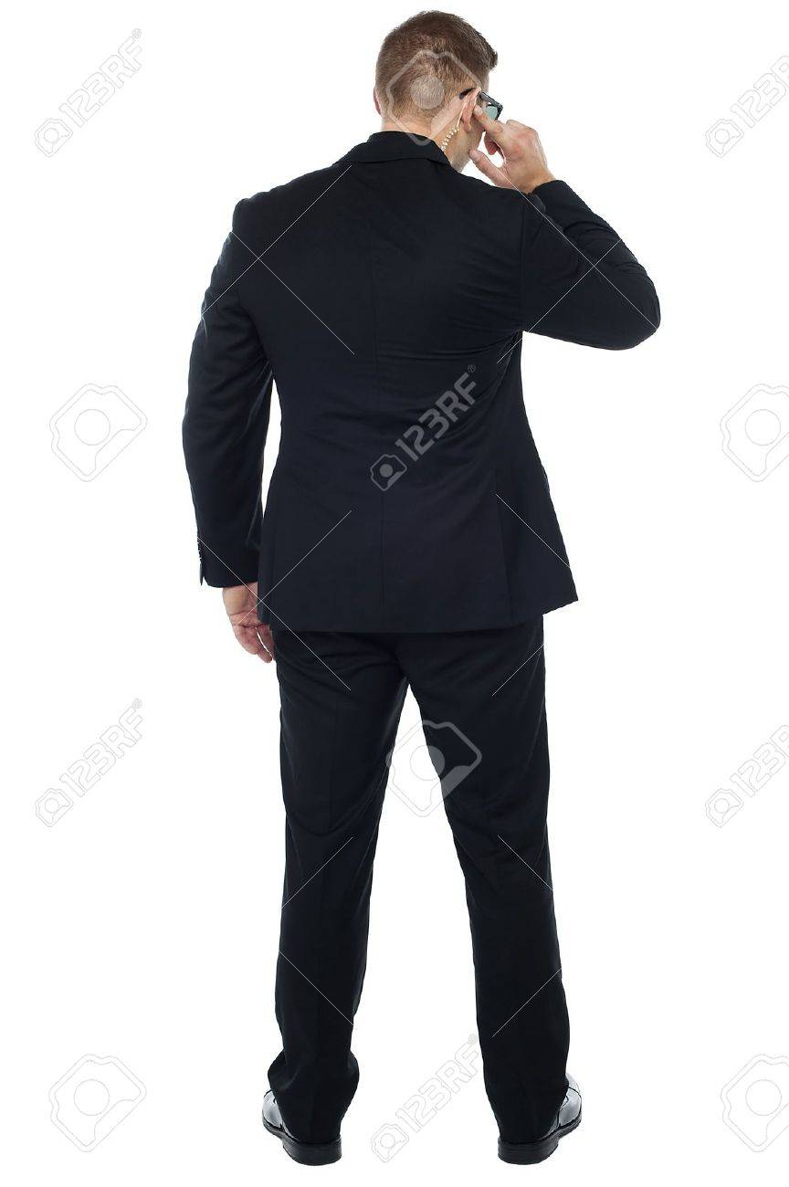 Back pose of young male security person holding earpiece and listening carefully Stock Photo - 15351631