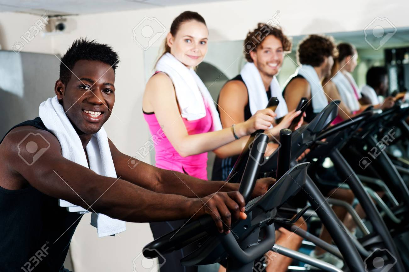 Energetic group working out together in a gym on elliptical Stock Photo - 15440551