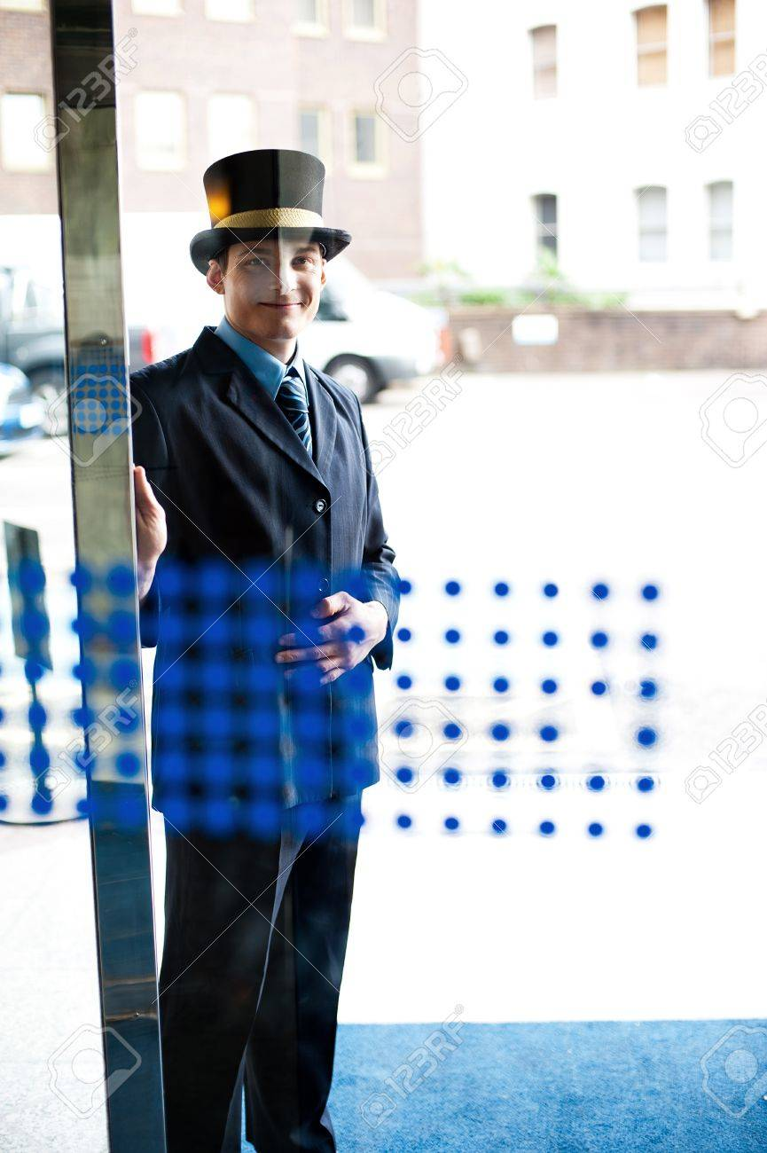 Hotel doorman at your service. Buildings and cars in the background Stock Photo - 15578279