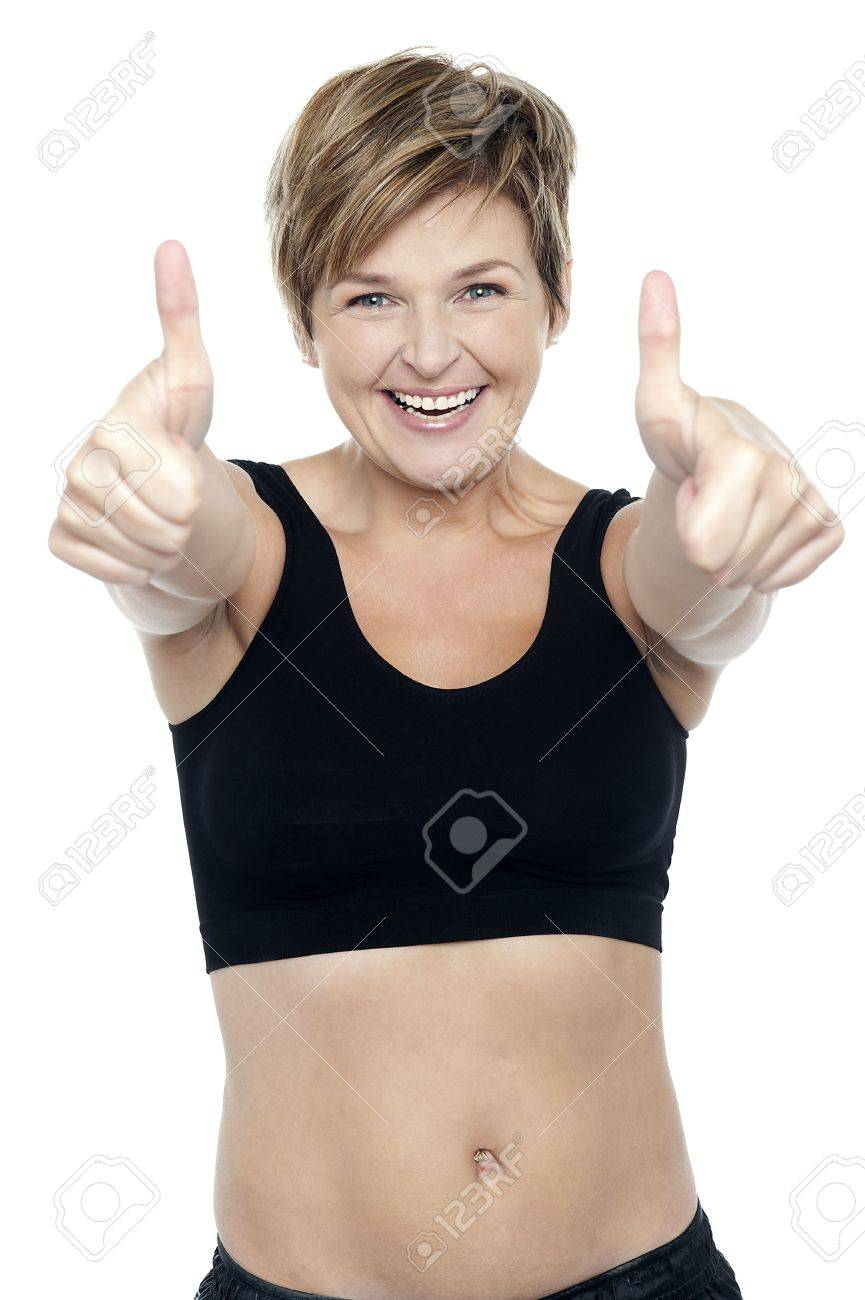 Attractive fit lady in workout wear showing double thumbs up to camera Stock Photo - 16167283