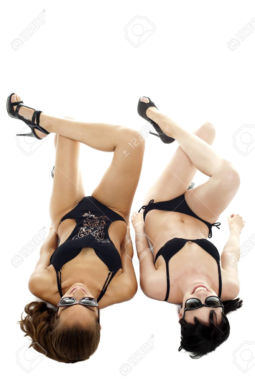Hot bikini clad models relaxing. Indoor shot. All on white background. Stock Photo - 16469248