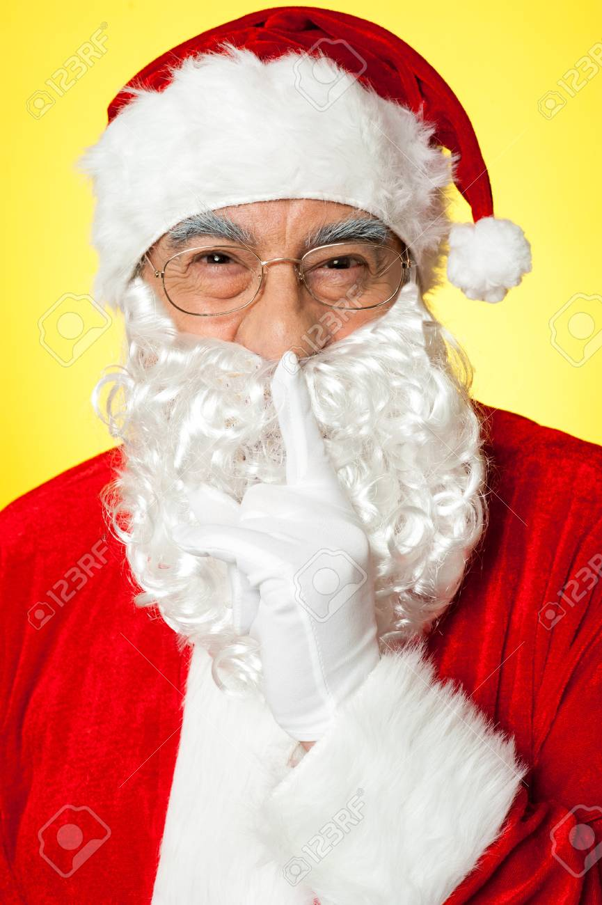 Shh...Aged Santa gesturing silence. Closeup over yellow background. Stock Photo - 16511164