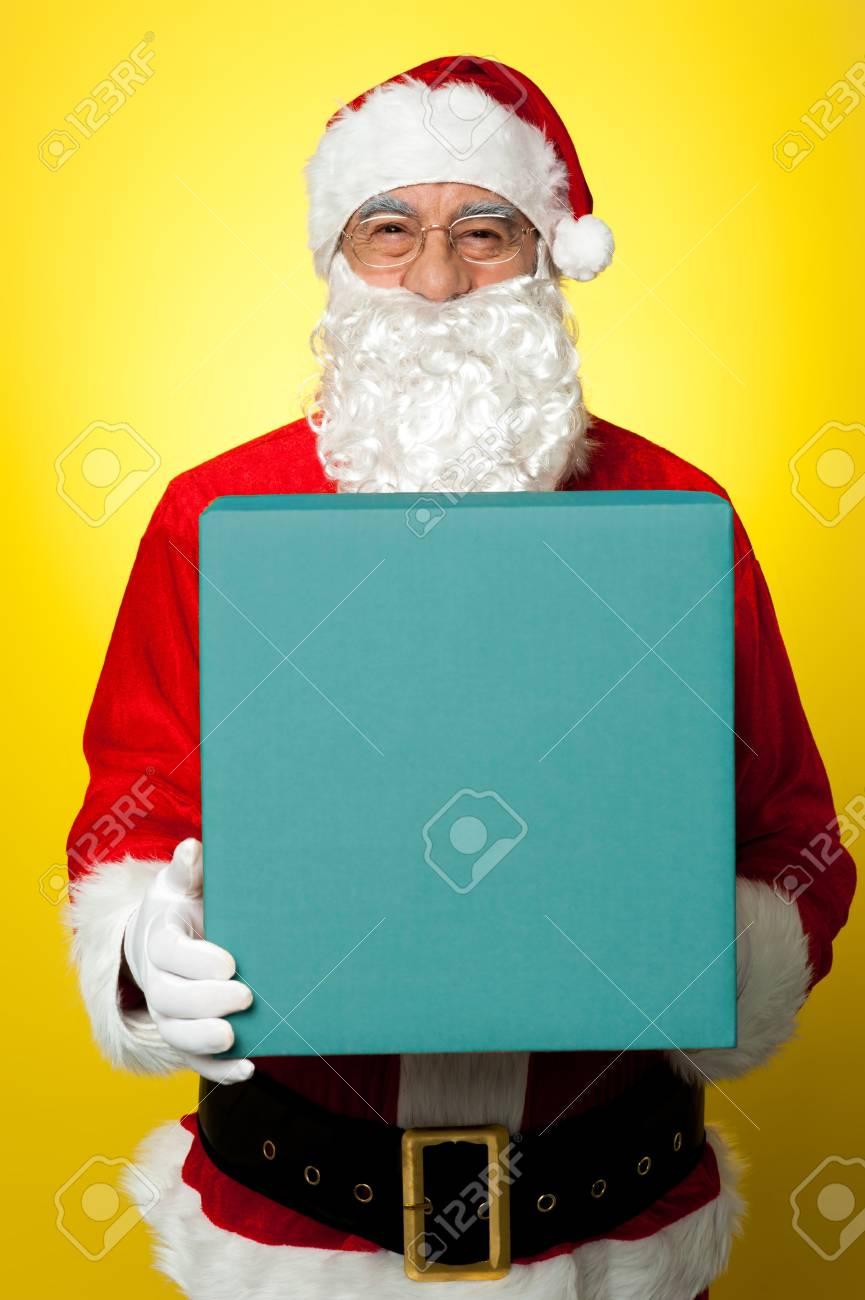 Isolated smiling Santa holding gift box and looking at camera. Stock Photo - 16510650