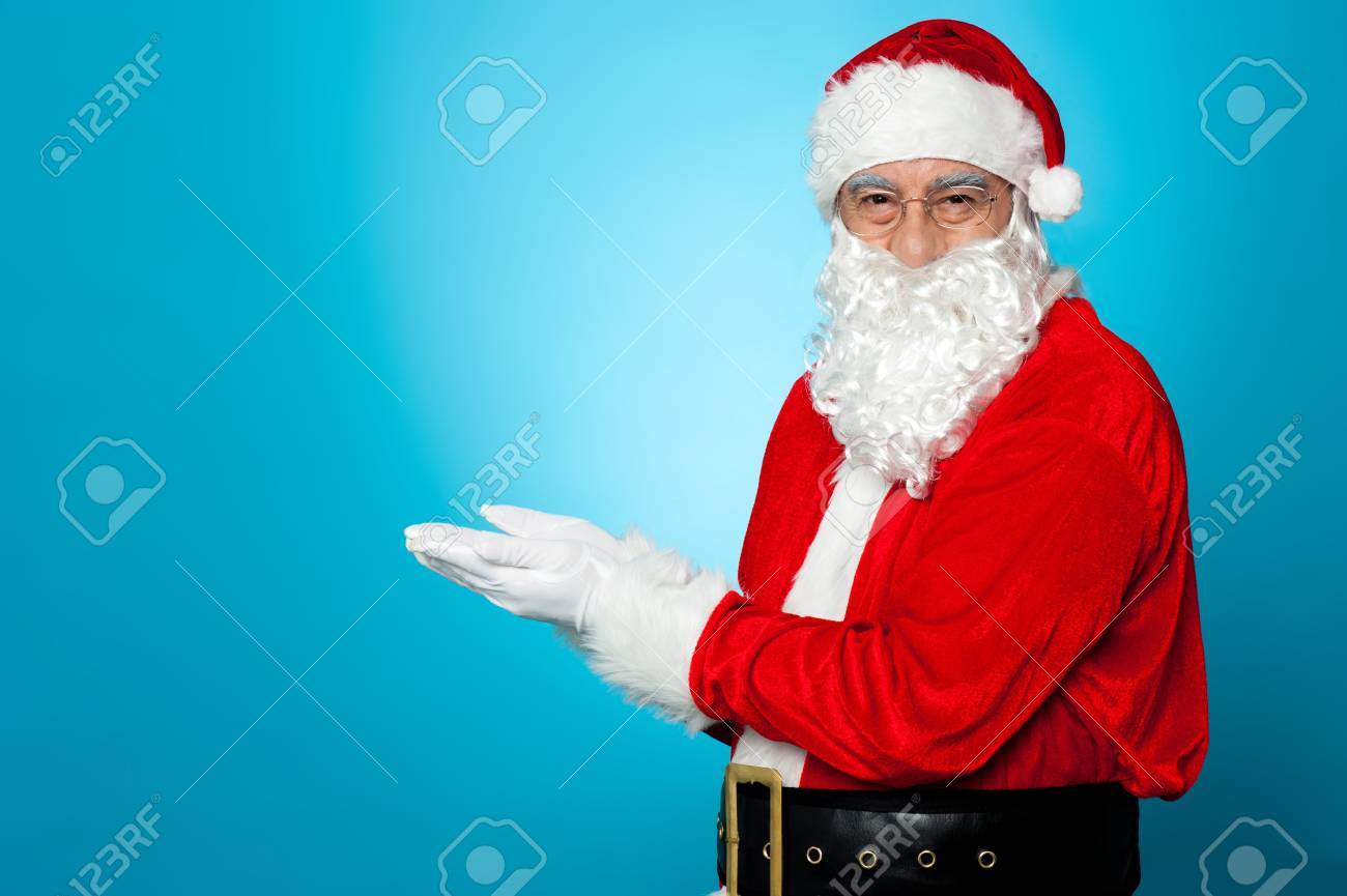 Santa against blue background posing with open palms. Copy space concept. Stock Photo - 16510555