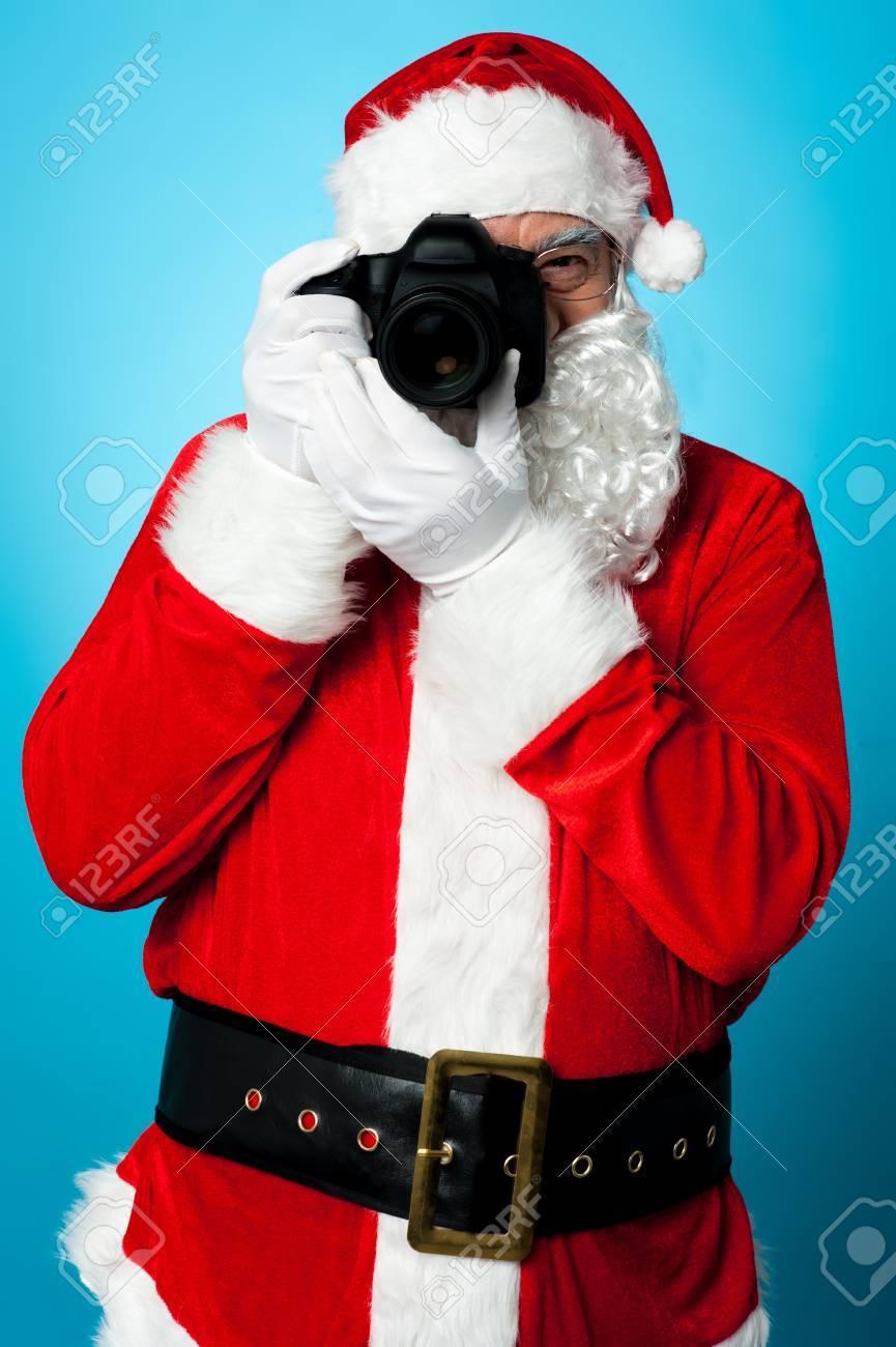 Smile Please! Santa Claus turns into a pro photographer. Stock Photo - 16511116