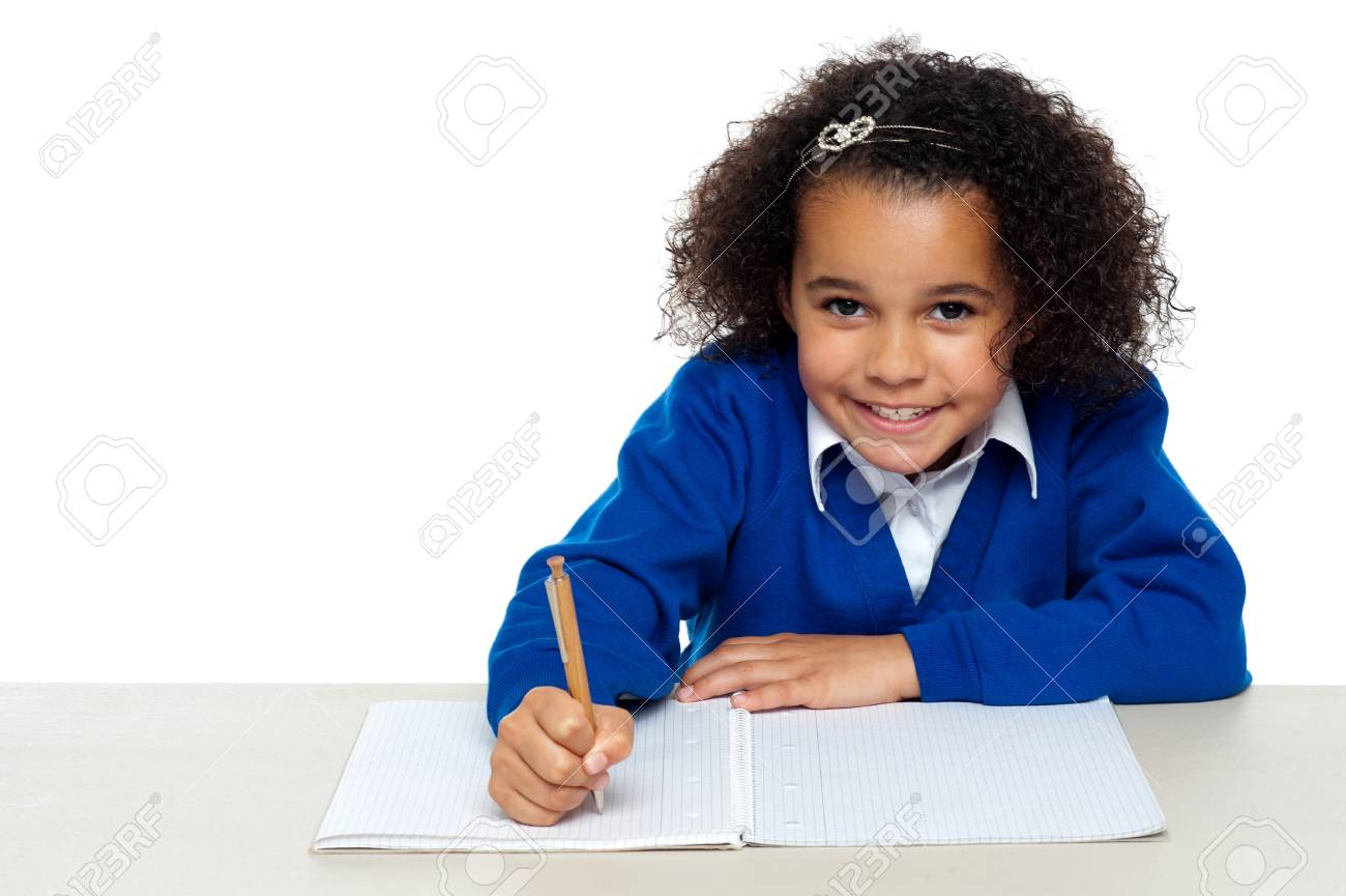 Studio shot of a cute primary kid writing her assignment. Stock Photo - 16771523