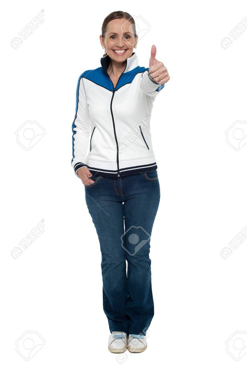 Casual charming woman gesturing thumbs up. Full length studio shot. Stock Photo - 17204207