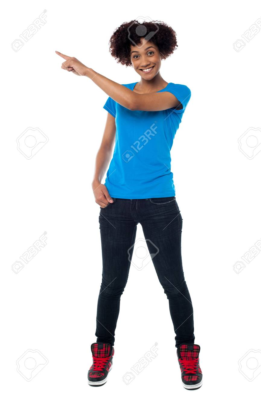 Cheerful young model in trendy wear indicating towards copy space area. Stock Photo - 17378495
