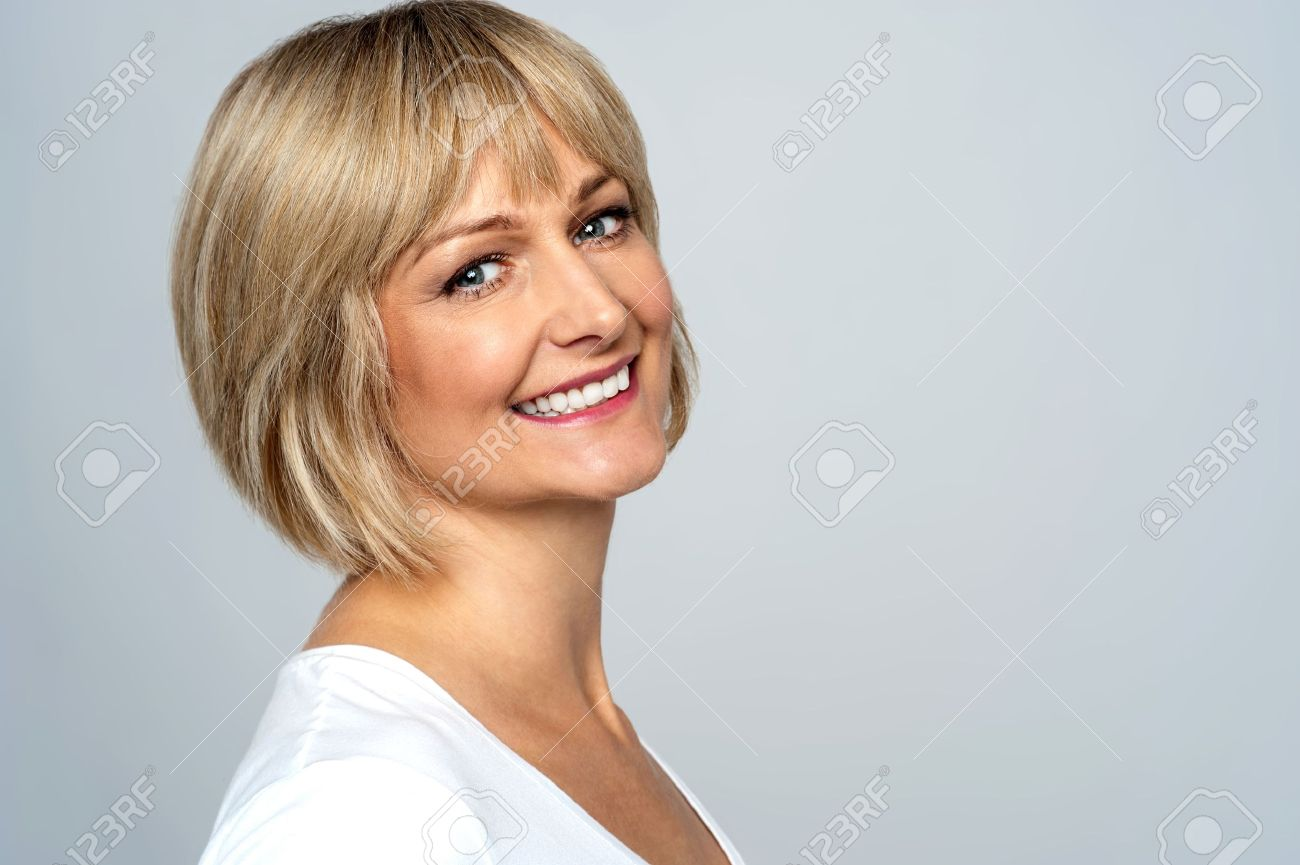Pretty middle aged lady posing over grey background Stock Photo - 20667074