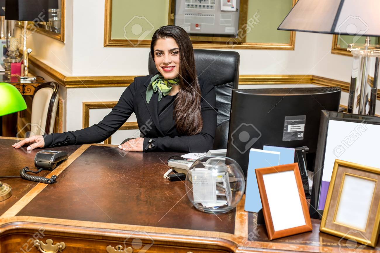 Jeune jolie réceptionniste à son bureau banque dimages et photos